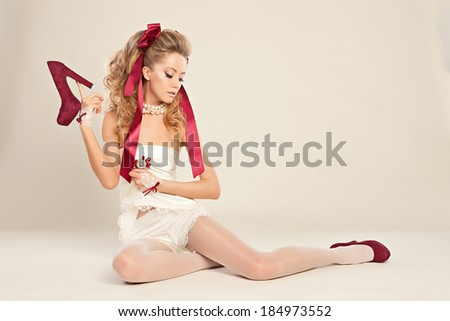 Young woman  in the doll style with red bow and red shoes  sitting on the floor. Studio photography . - stock photo