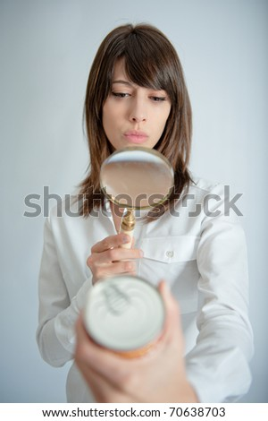 Young woman inspecting a can?s nutrition label with a magnifying glass