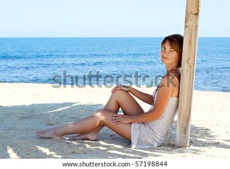 young woman resting under a straw  umbrella on a beach near the sea - stock photo