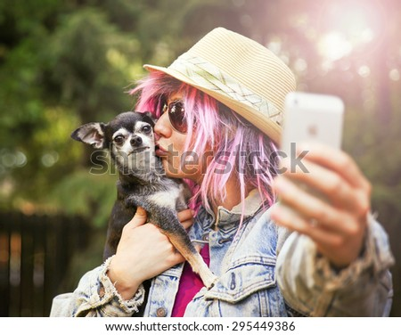 Young woman taking a selfie with a cute chihuahua dog toned with a retro vintage instagram filter effect app or action - stock photo