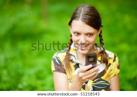 Young woman using her phone at  park.