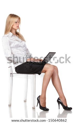 Young woman with a laptop sitting in full length  isolated on white background