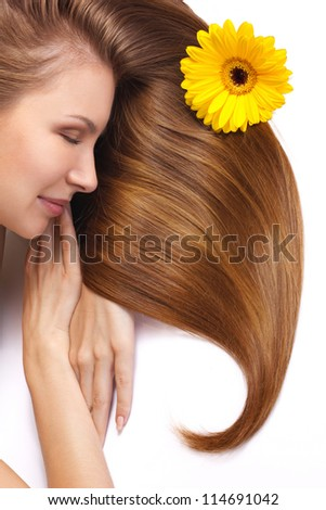 young woman with flower in beautiful long shining hair sleeping isolated on white - stock photo