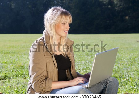 young woman with laptop on a meadow - stock photo