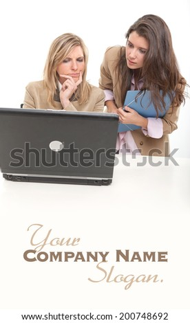 2 young women at work around a computer  - stock photo