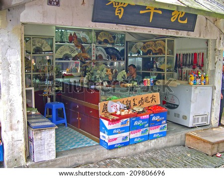 ZHOUZHUANG, SHANGHAI-SEPTEMBER 25, 2005: man running a souvenirs shop. Zhouzhuang water village is Shanghai tourist attraction with 1000000 visitors year        - stock photo