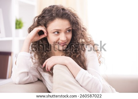 �?��¸��´ ��·��±��¾��º��?. Young smiling woman is sitting on a couch at home. Close-up. - stock photo