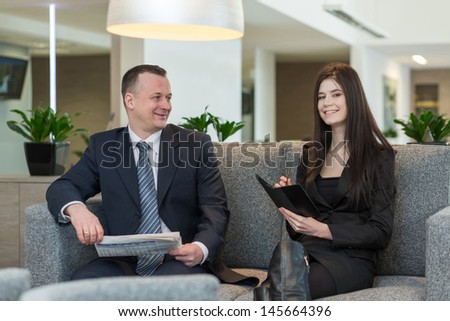 A a man with newspaper and girl with notepad talking about business, focus on a girl.
