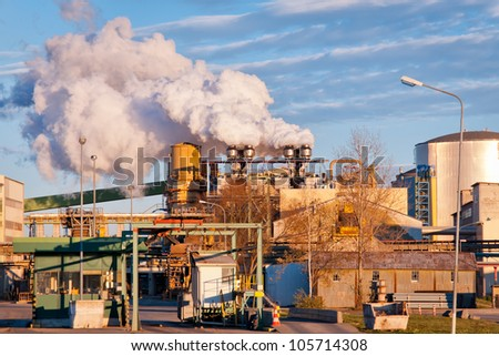 A A sugar mill factory creating smoke in front of a blue sky