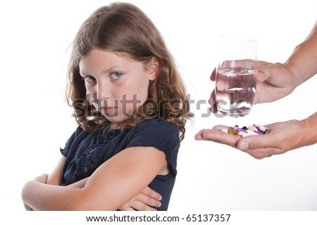 A adorable little girl with a sad face turns away from her parent, unwilling to take the medicine pill being offered - stock photo