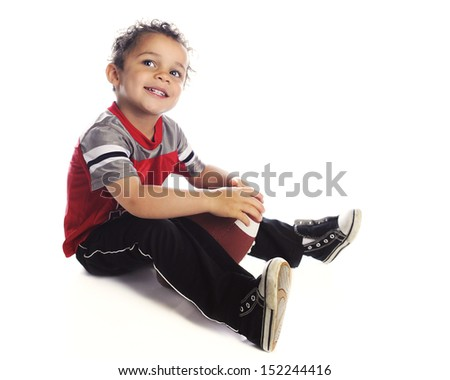 A adorable preschooler happily looking up as he sits with his football.  On a white background.