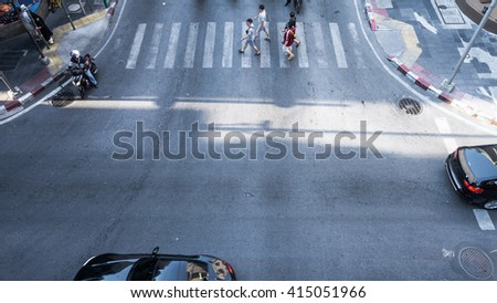 A aerial view of  the high traffic on a street intersection with crosswalk. - stock photo