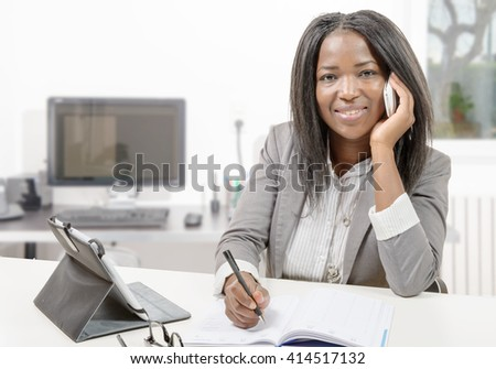 a african american business woman working with tablet and phone - stock photo
