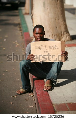 "a african american male model holds a cardboard sign that reads ""will model for food"" - stock photo"