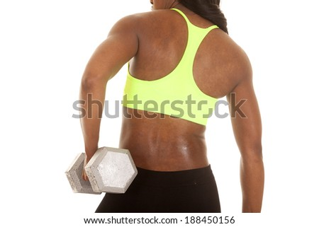 a African American woman showing off her back. She is working out with weights. - stock photo