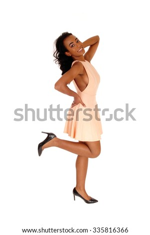 A african american women, standing on one leg in profile in a beige dress,isolated for white background. - stock photo