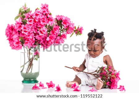 A African infant dressed in white on the table and play with pink flowers. - stock photo