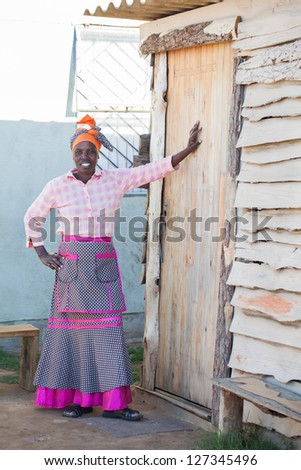 A African woman staning infront of the door of her home. - stock photo