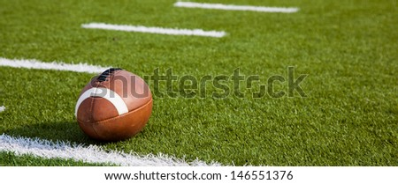 A American football on a green football field - stock photo