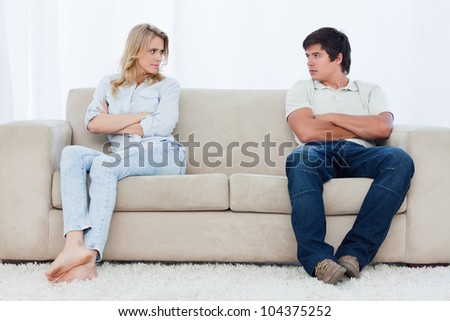 A angry couple sit at the two ends of the couch with their arms folded looking at each other
