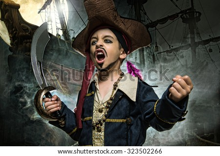 A angry young boy wearing a pirate costume. He stands on the background of the ship  - stock photo