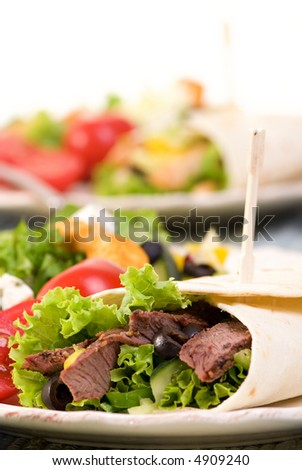 A appetizing beef steak wrap with lots of vegetables and a side salad.