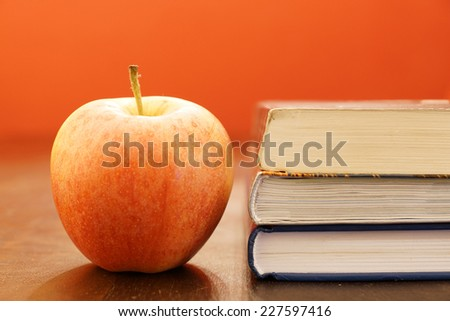 A apple and a book on a wooden table - stock photo