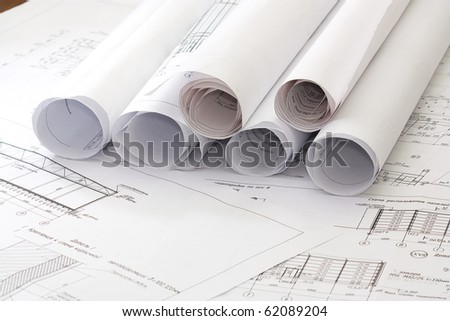 A architect's workspace with plans and designs - stock photo