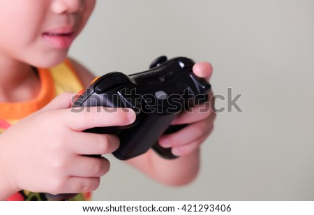 A asian boy holding game controller playing video games - stock photo