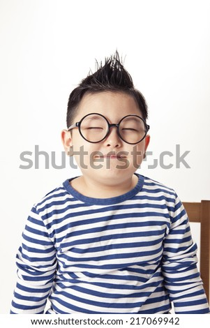 A asian boy portrait wearing black glasses and blue stripes with smile. - stock photo
