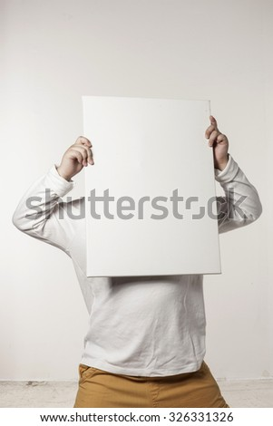 A asian(japan, chinese, korea) pretty boy(kid, children) hold a white(blink, empty) canvas frame with a smile isolated white at the studio.