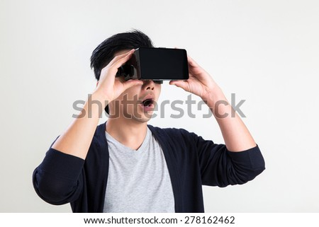 A asian man wearing virtual reality goggle. - stock photo
