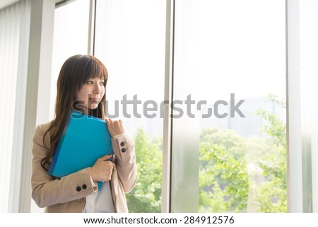 A asian woman holding files