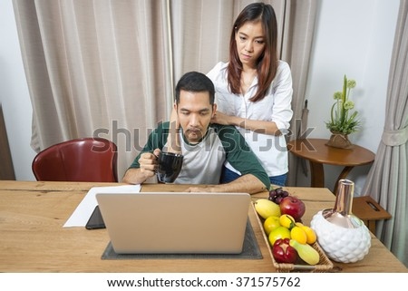 A asian Young couple in kitchen looking at notebook pc. Man sitting by his girlfriend standing in morning. - stock photo