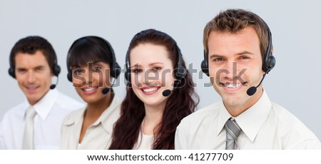 a attractive team with a headset on working a call center at the camera - stock photo