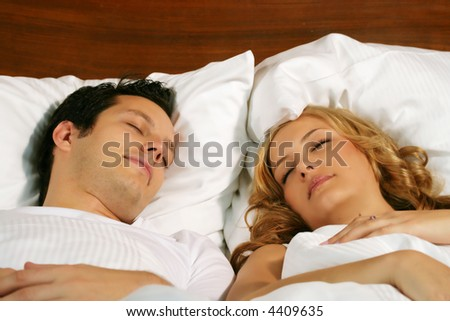a attractive young couple is sleeping in there bed at home - stock photo