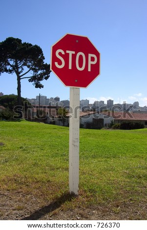 A authoritatively low angle view of stop sign against an urban backdrop.