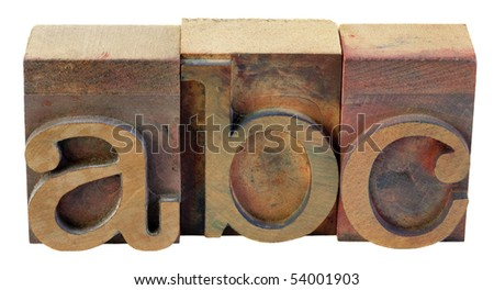 a, b, c - first letters of alphabet in vintage wooden letterpress type blocks, stained by color inks, isolated on white - stock photo
