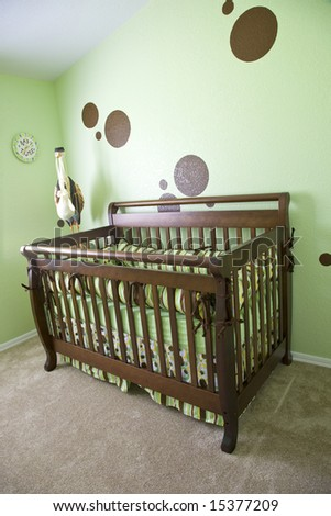 A babies room with green walls and brown dots.