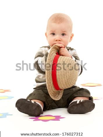 A baby boy chews on a straw hat. - stock photo
