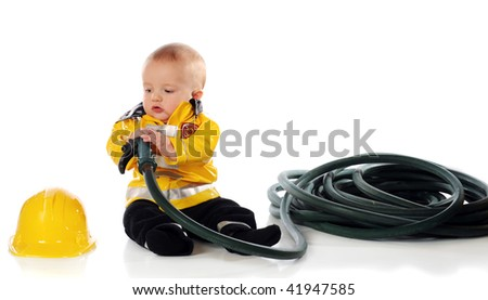 A baby boy in a fireman's suit, eying his hat while holding the nozzle and hose. - stock photo