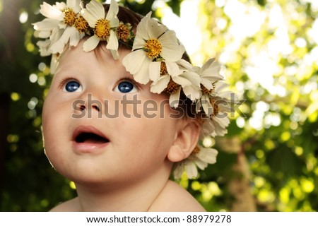 A baby boy in a flower wreath looking at something interesting - stock photo