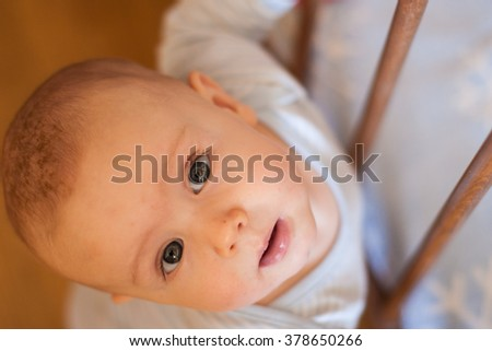 A baby boy looking up standing near his bed - stock photo