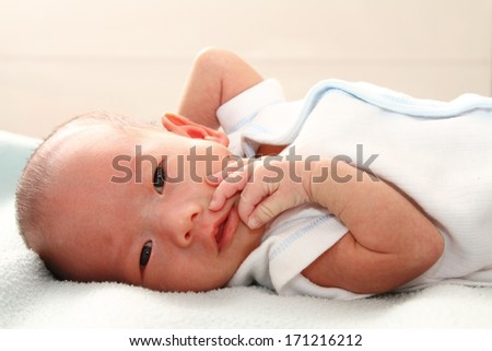A baby boy on a bed - stock photo