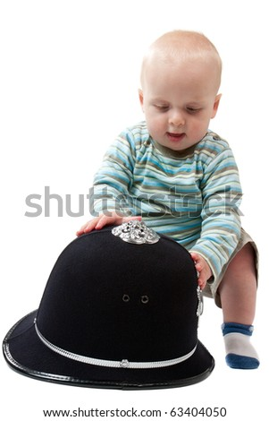 "A baby boy playing with a British police helmet.  ""The police are getting younger and younger!"""