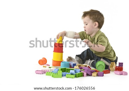 A baby boy playing with some plastic toys. - stock photo