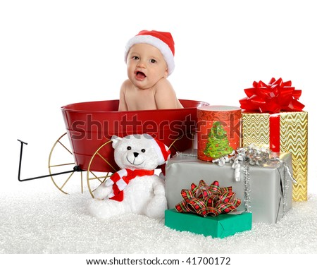 A baby boy sitting in a tiny red wagon with only a Santa hat, surrounded by wrapped Christmas gifts.  Isolated on white. - stock photo