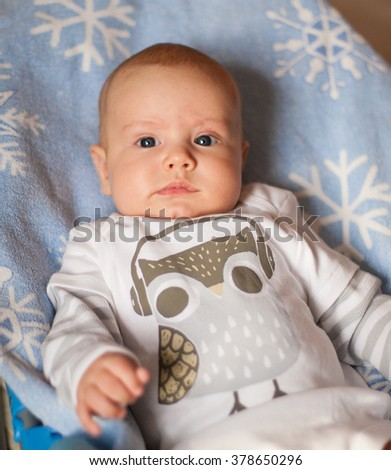 A baby boy wearing a bodysuit wih an owl lying on a blue blanket with snowflakes print - stock photo