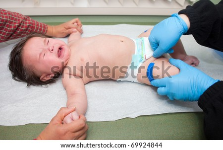 A baby crying after receiving a immunization shot - stock photo