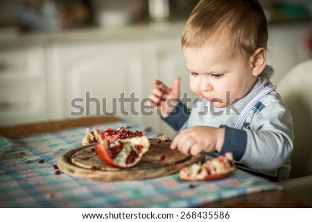 A baby eating a pomegranate fruit